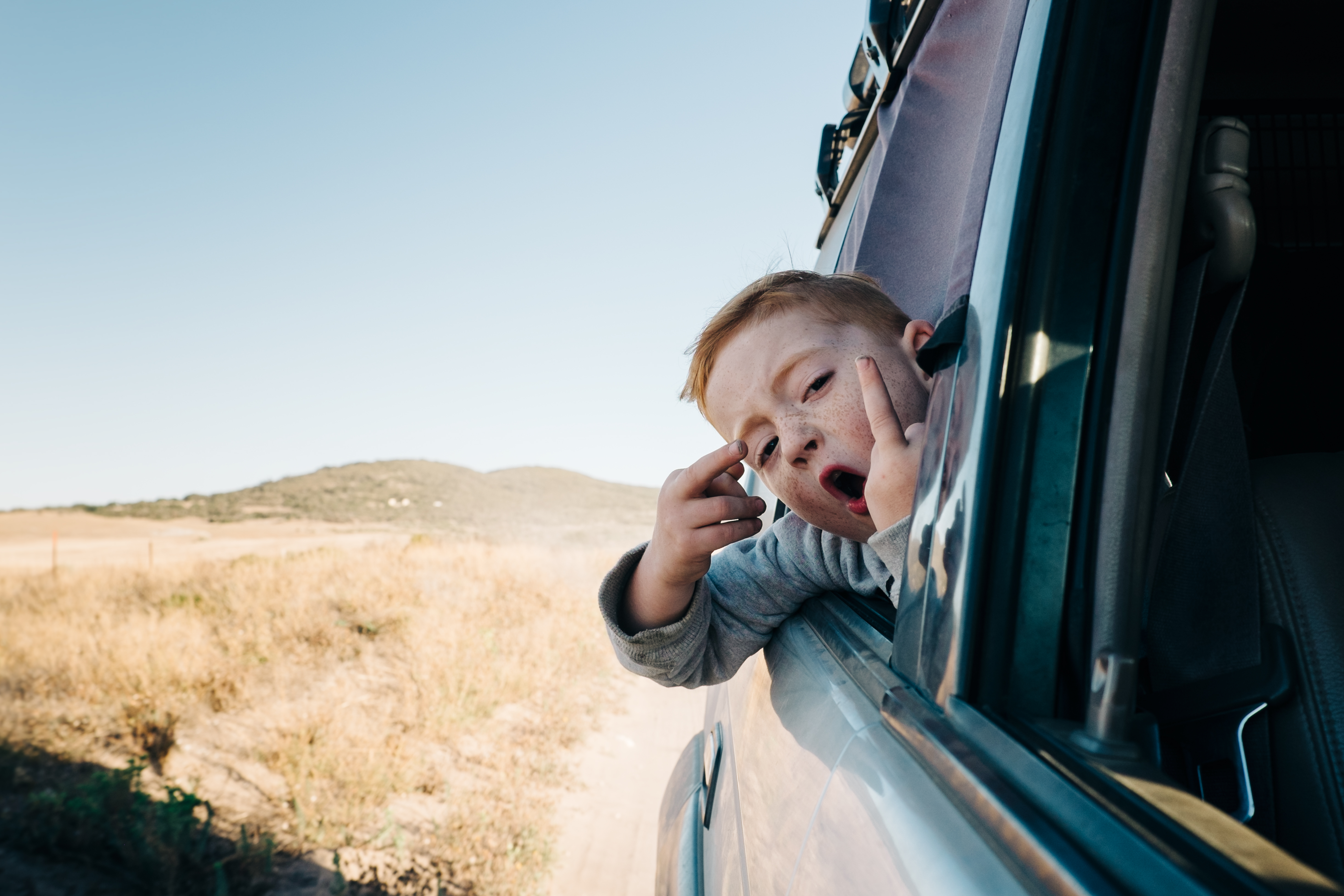 boy hanging out of car window