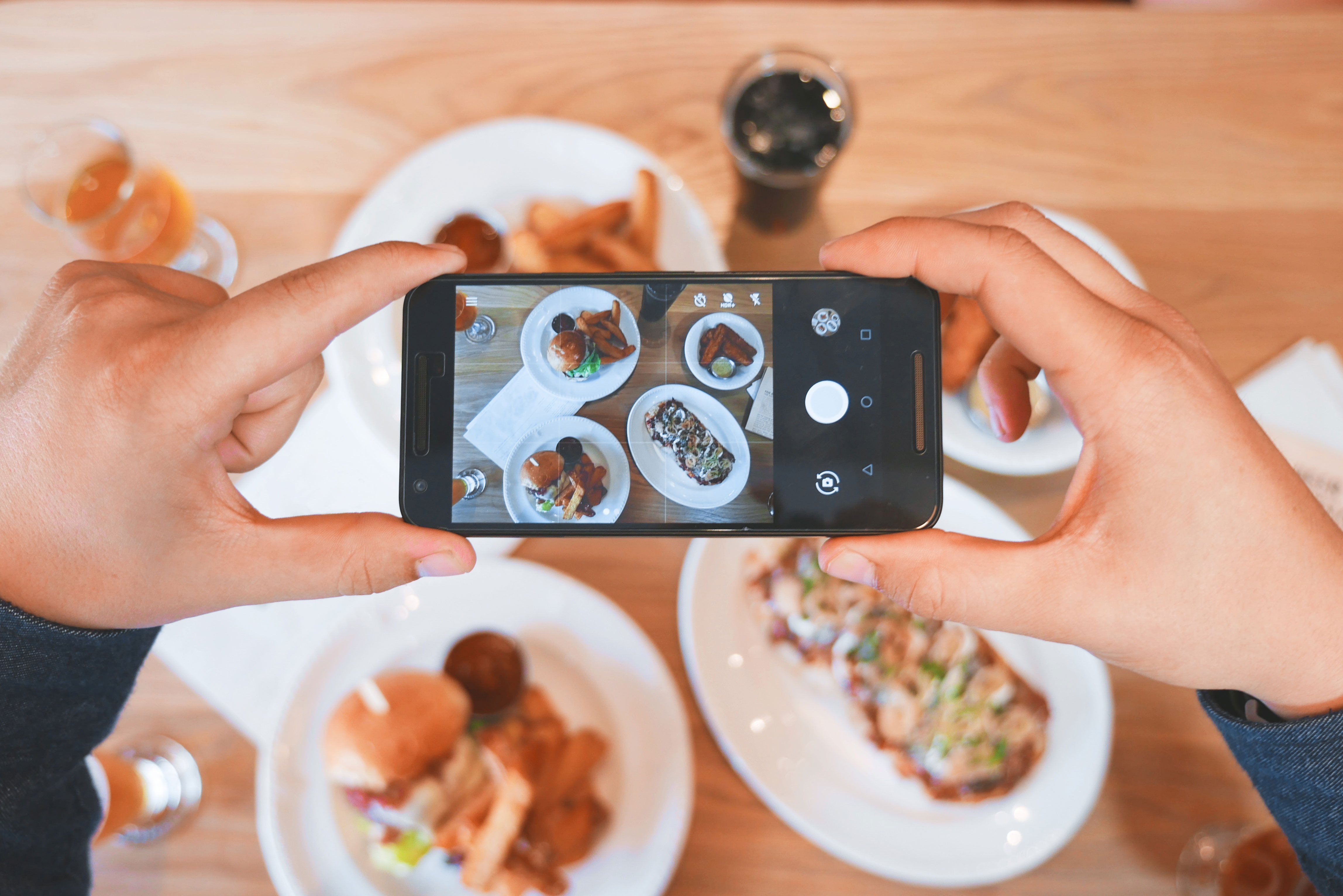 person taking photo of food with their phone