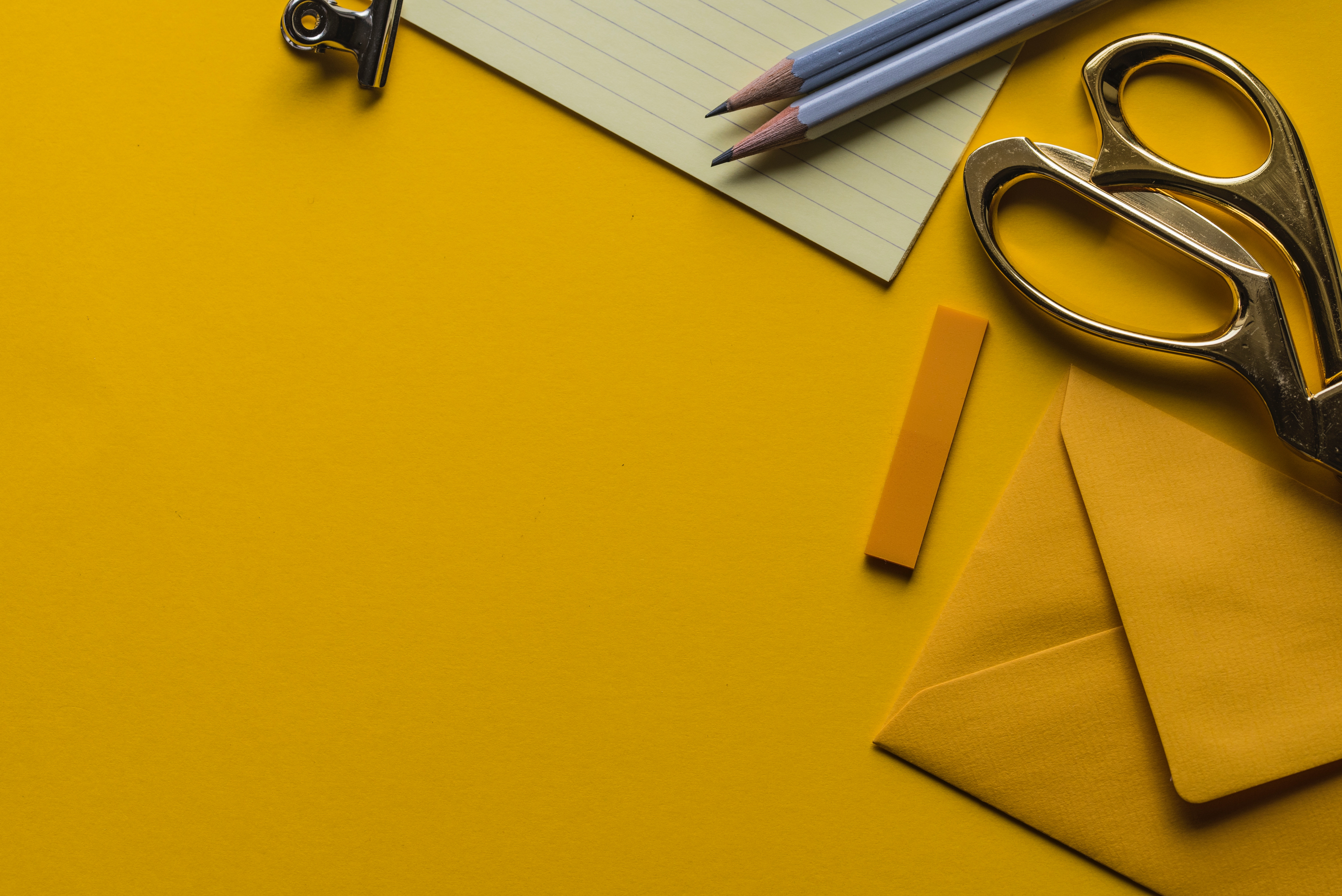 pencil, scissors and an envelope on bright yellow background
