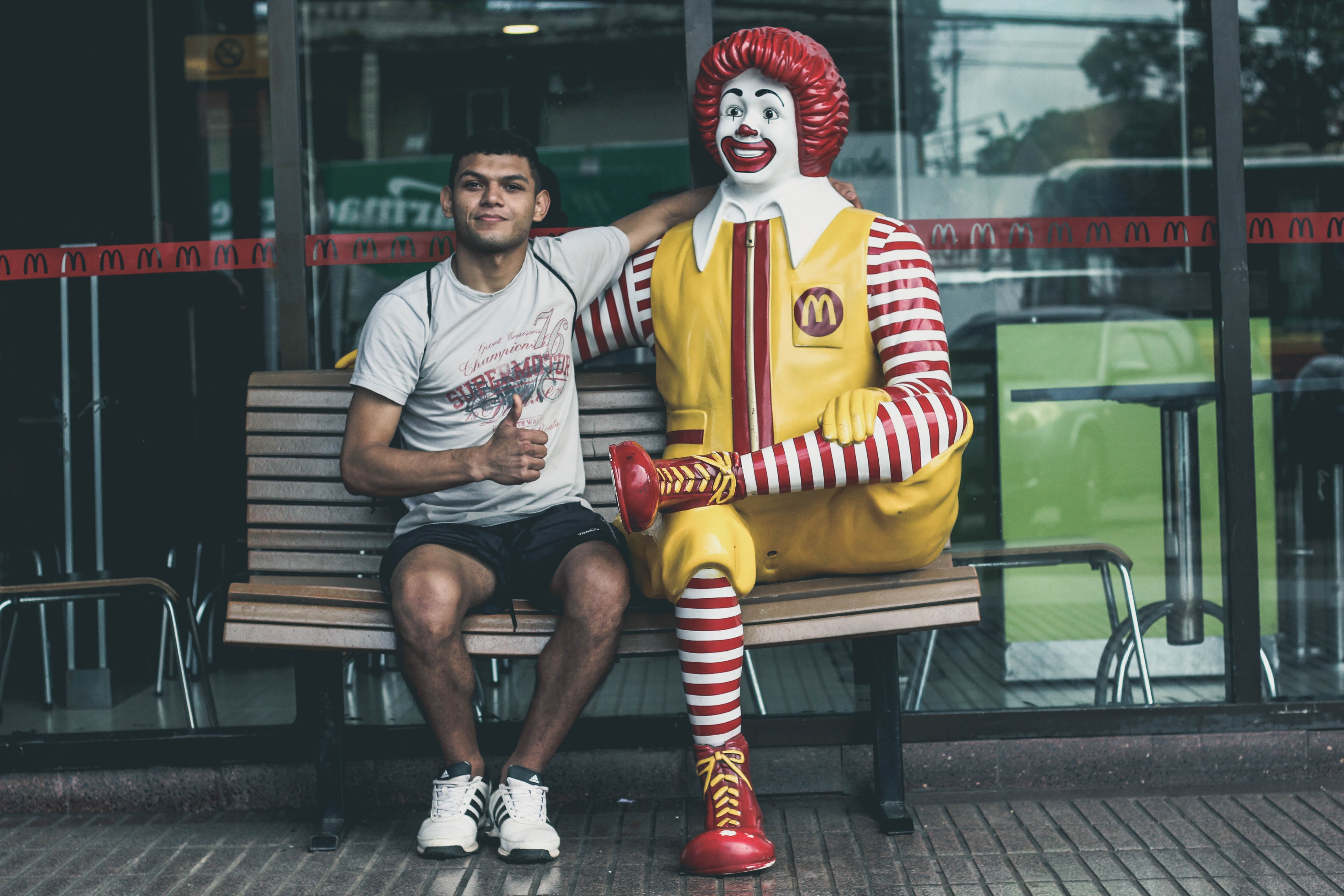 guy sitting with ronald mcdonald outside mcdonald's restaurant