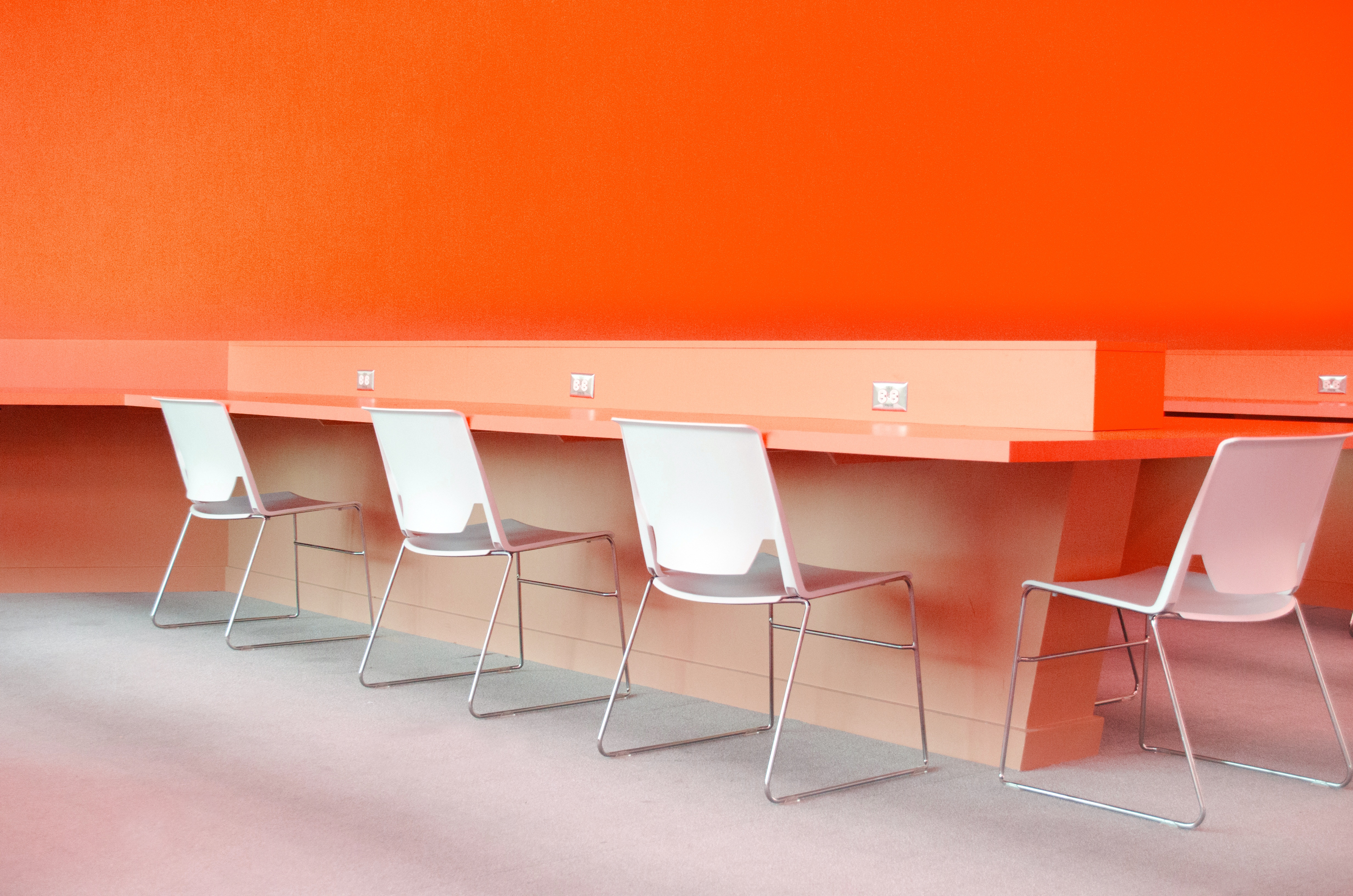 chairs and table in front of orange wall