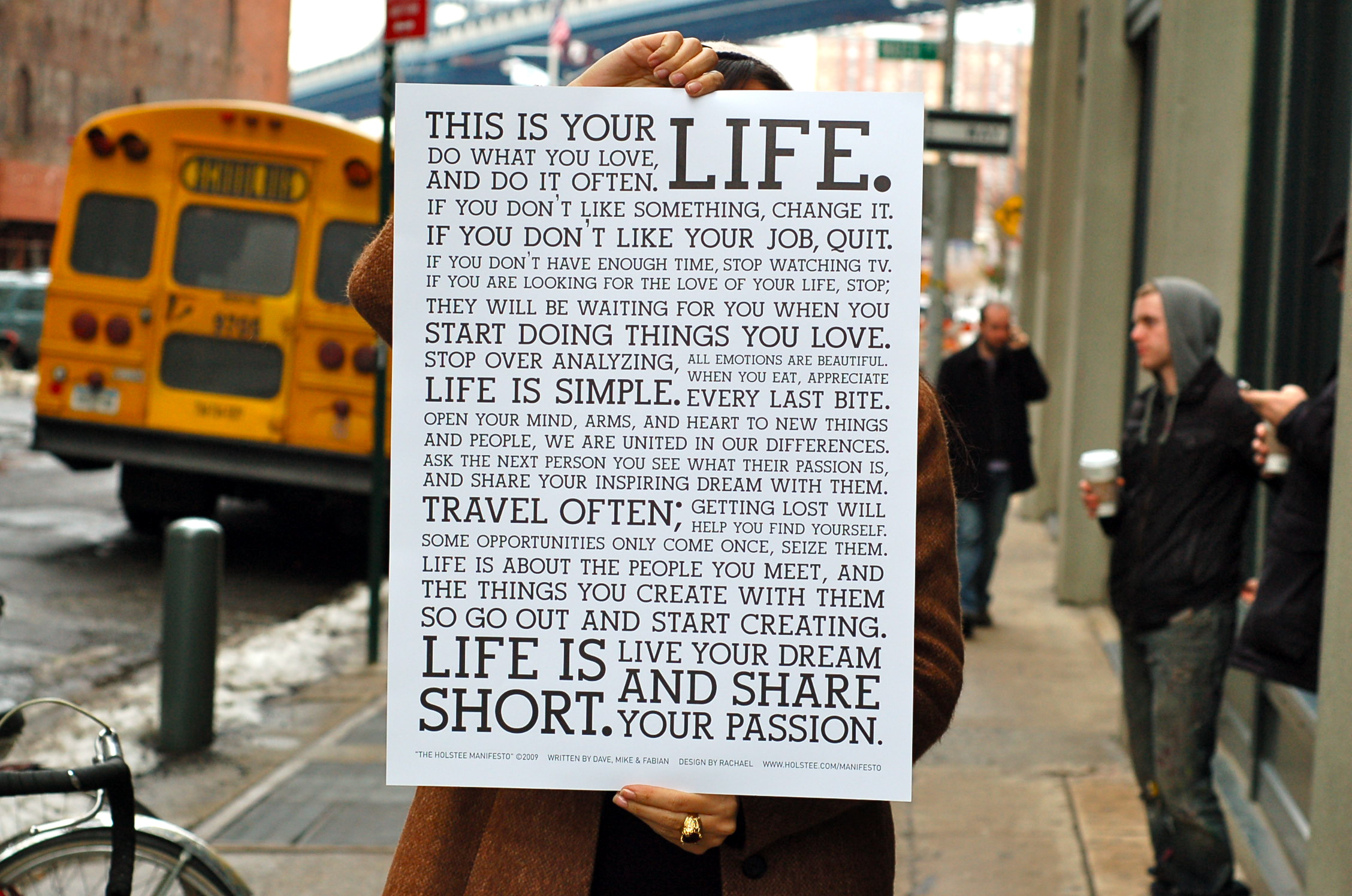 girl holding up holstee manifesto with yellow bus in background