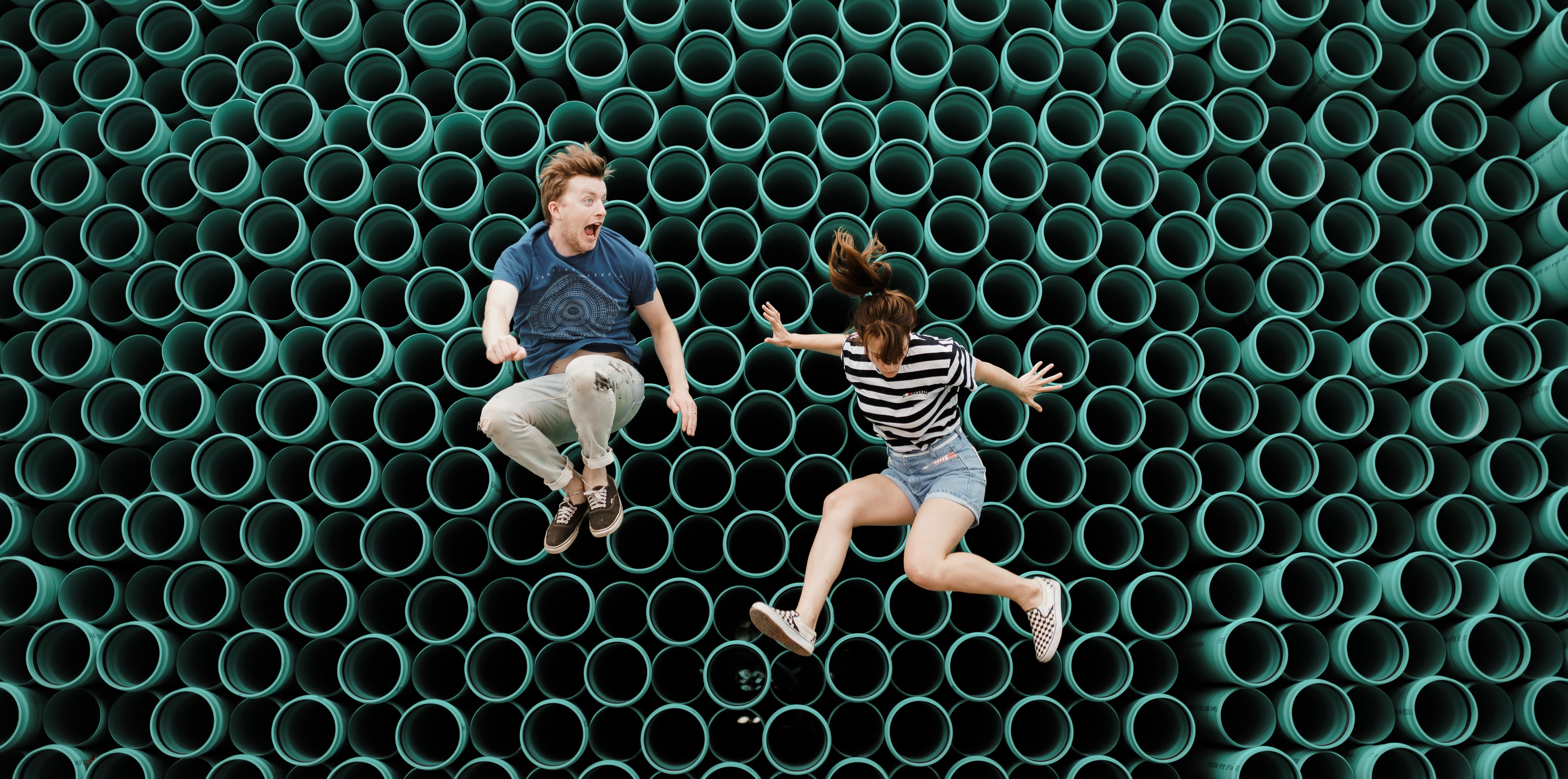 guy and girl jumping against textured wall