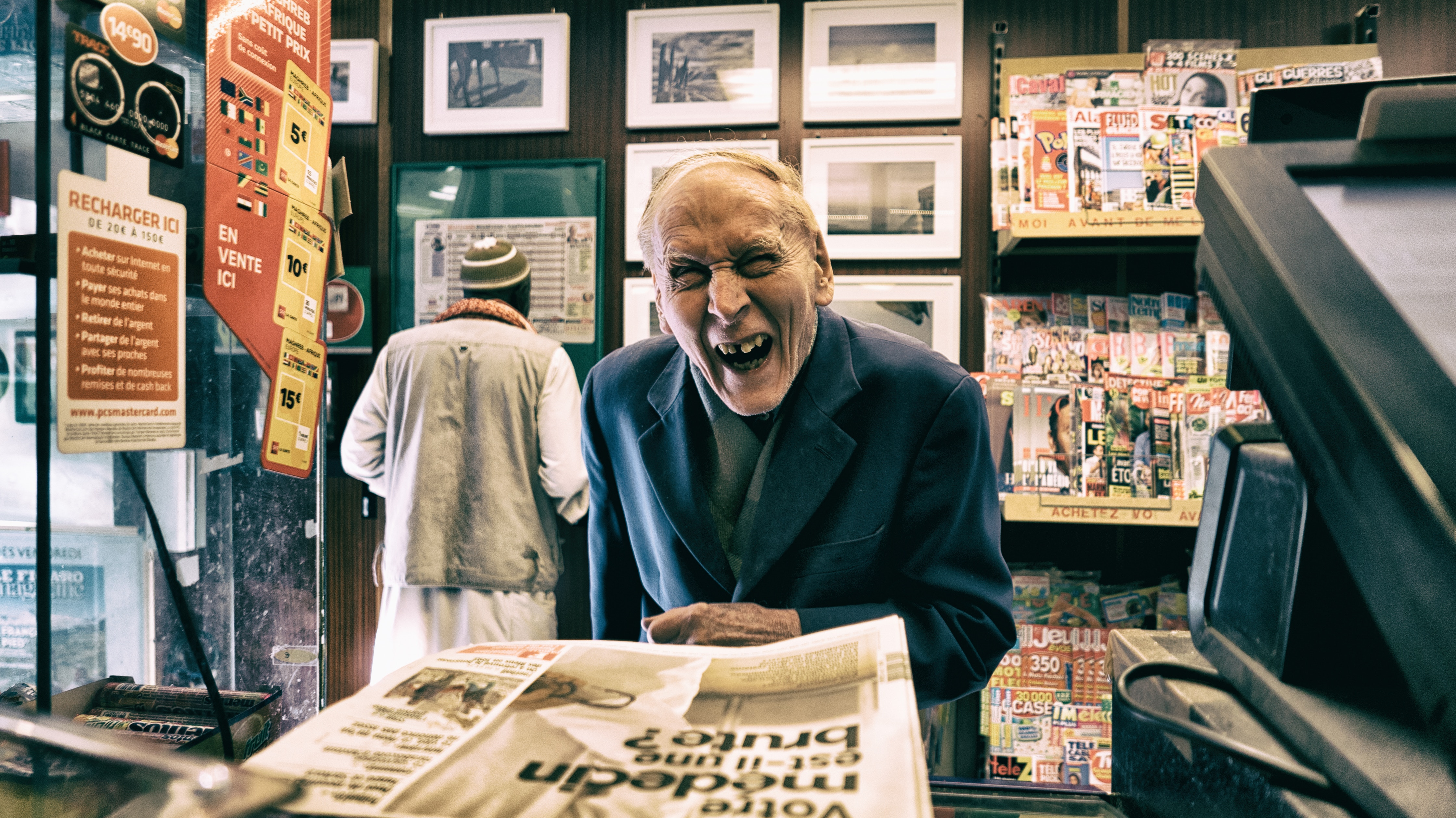 old man smiling in news agent