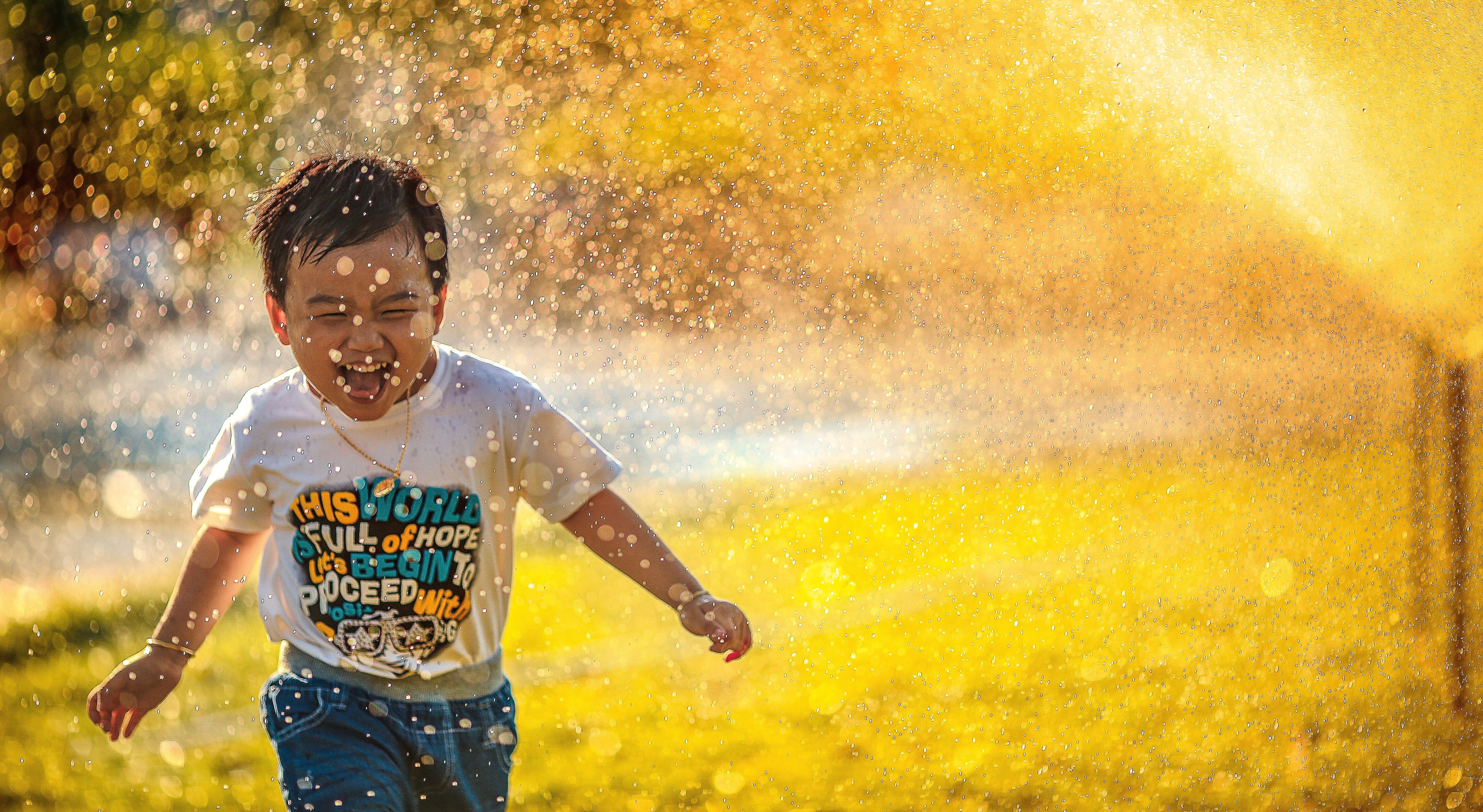 child plays in sprinkler