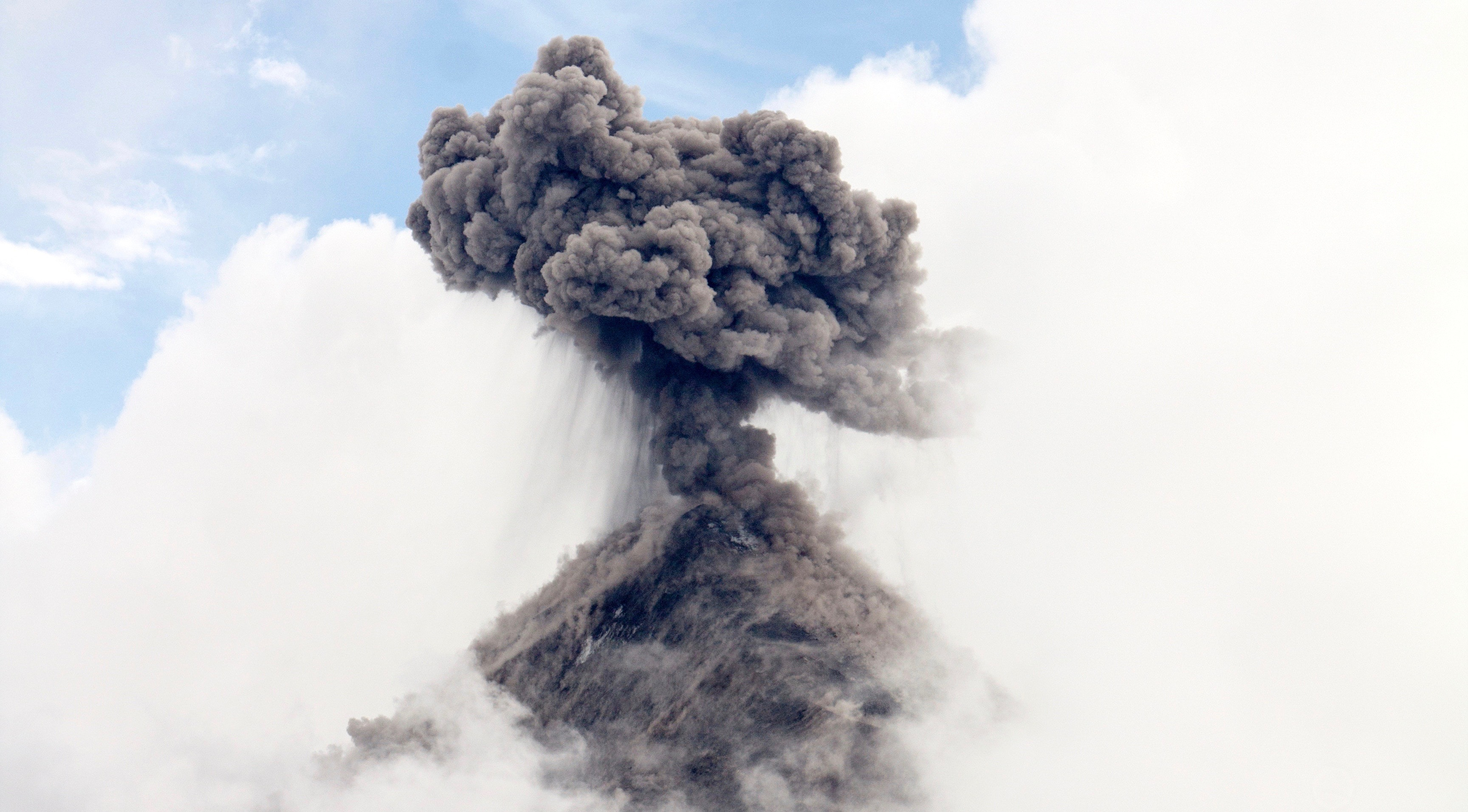 volcano erupting in cloud