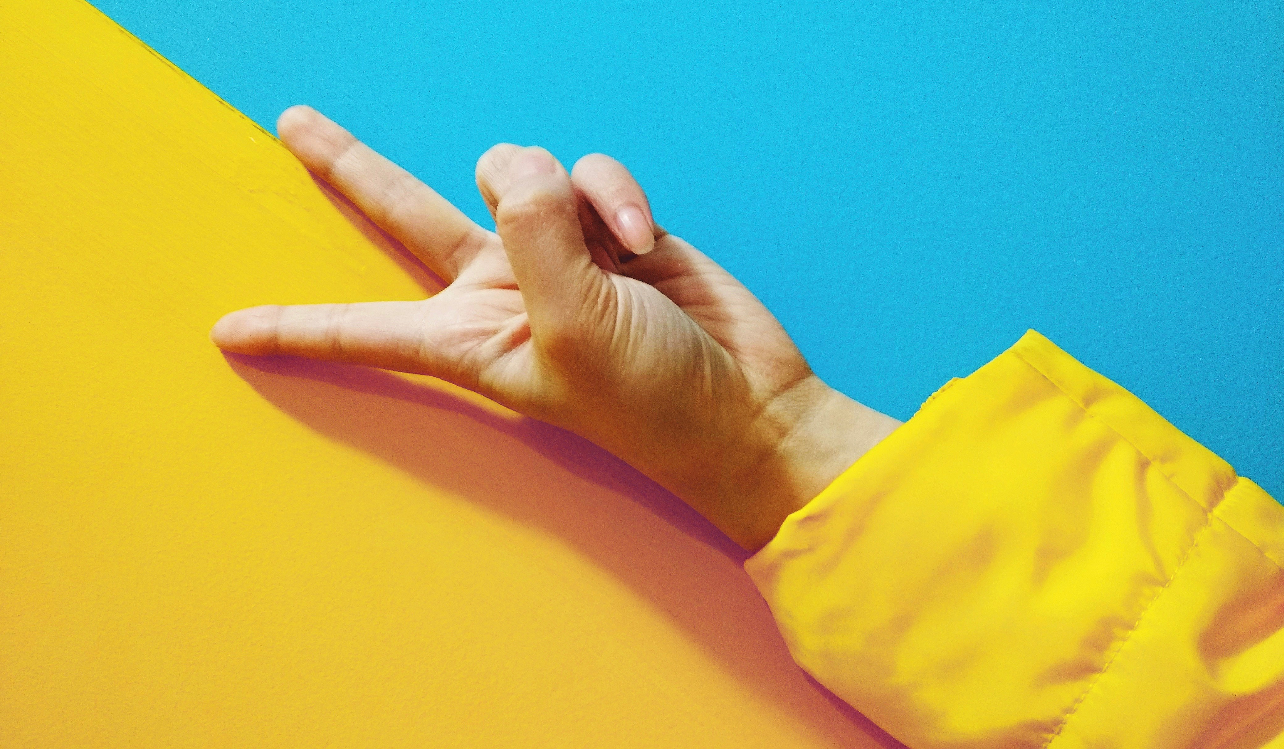 hand on blue and yellow background