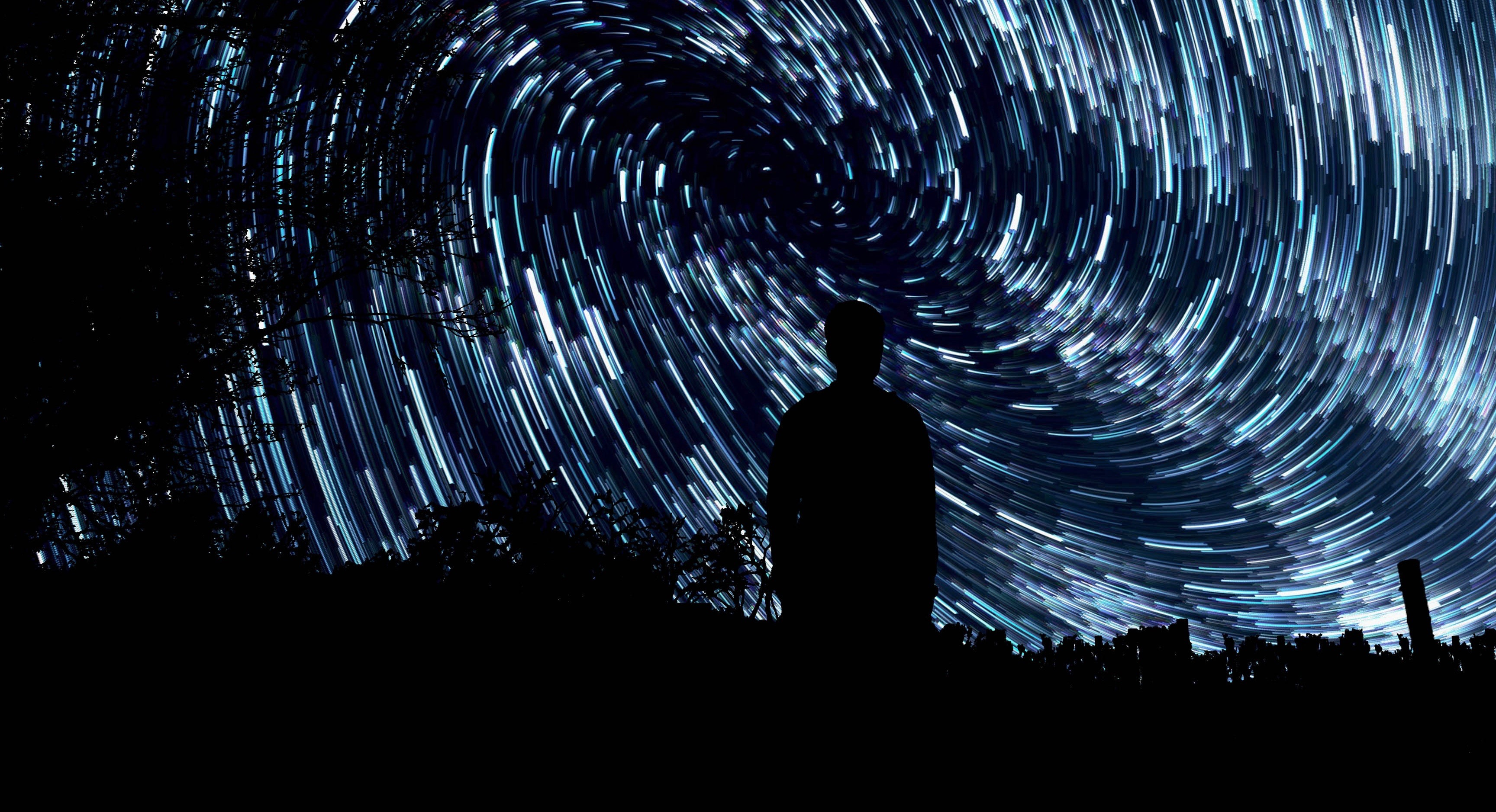 silhouette of man standing in front of stars