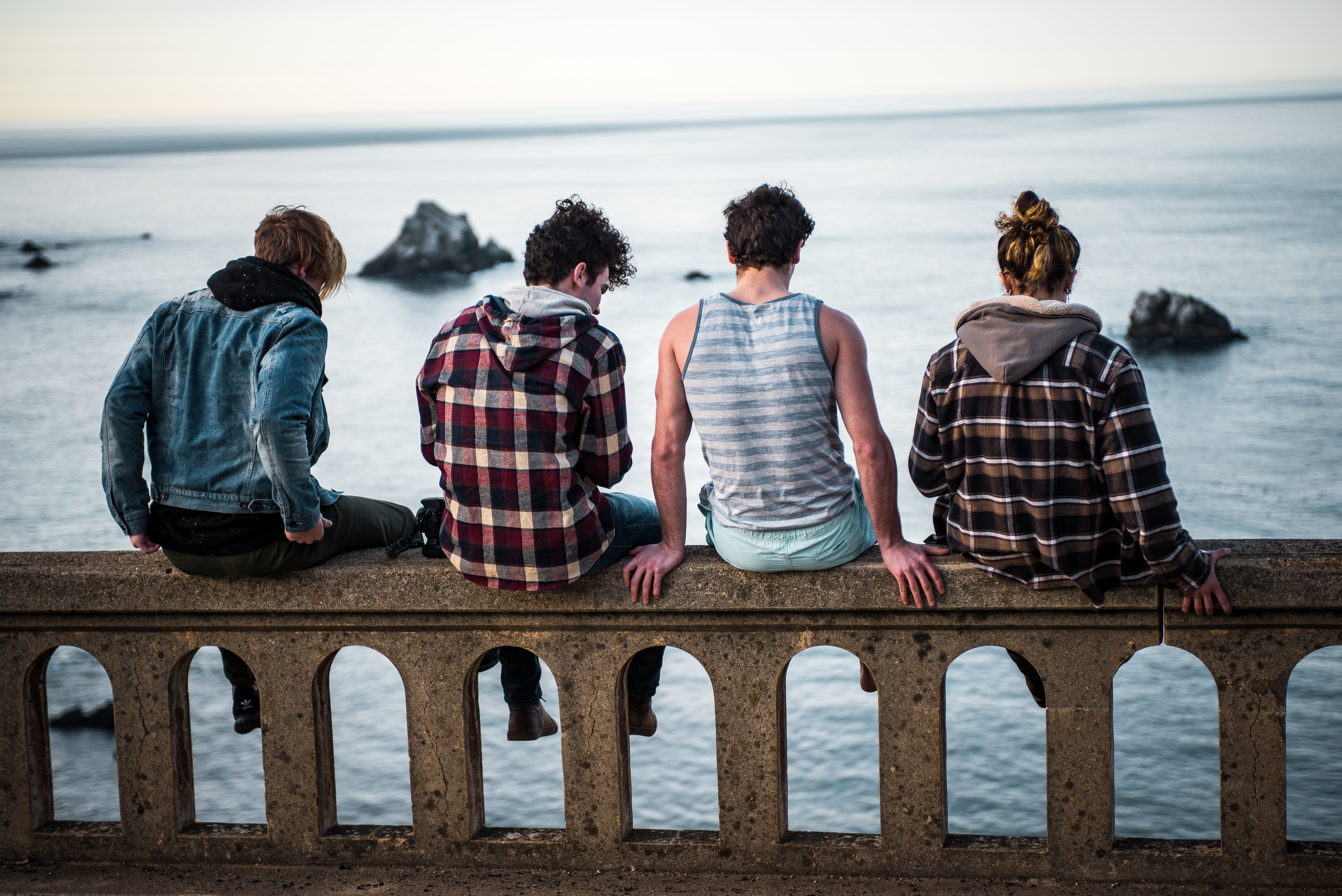 group of friends sitting on wall overlooking ocean