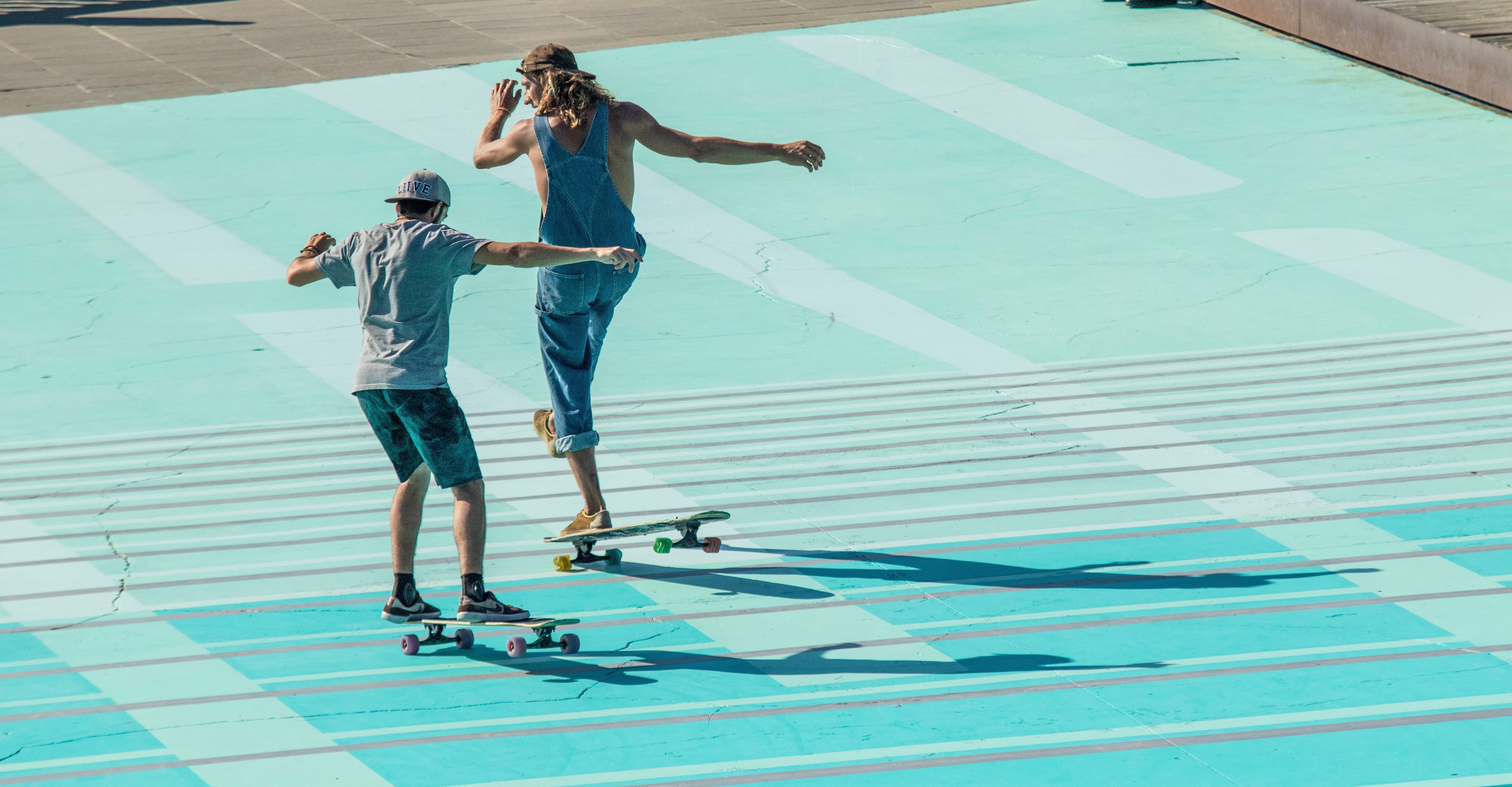 two guys playing on skateboards on light blue ground