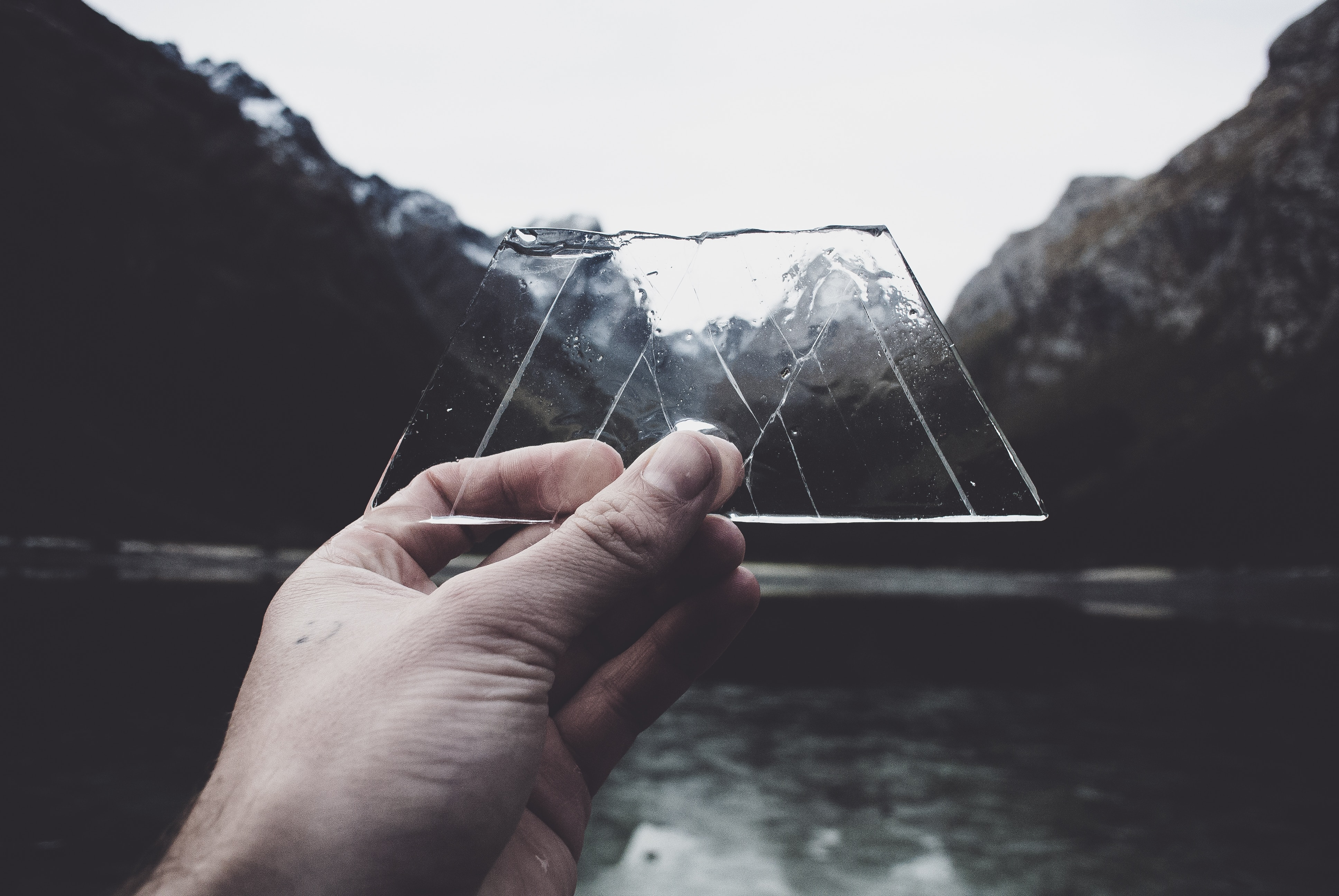 hand holding ice in front of mountains