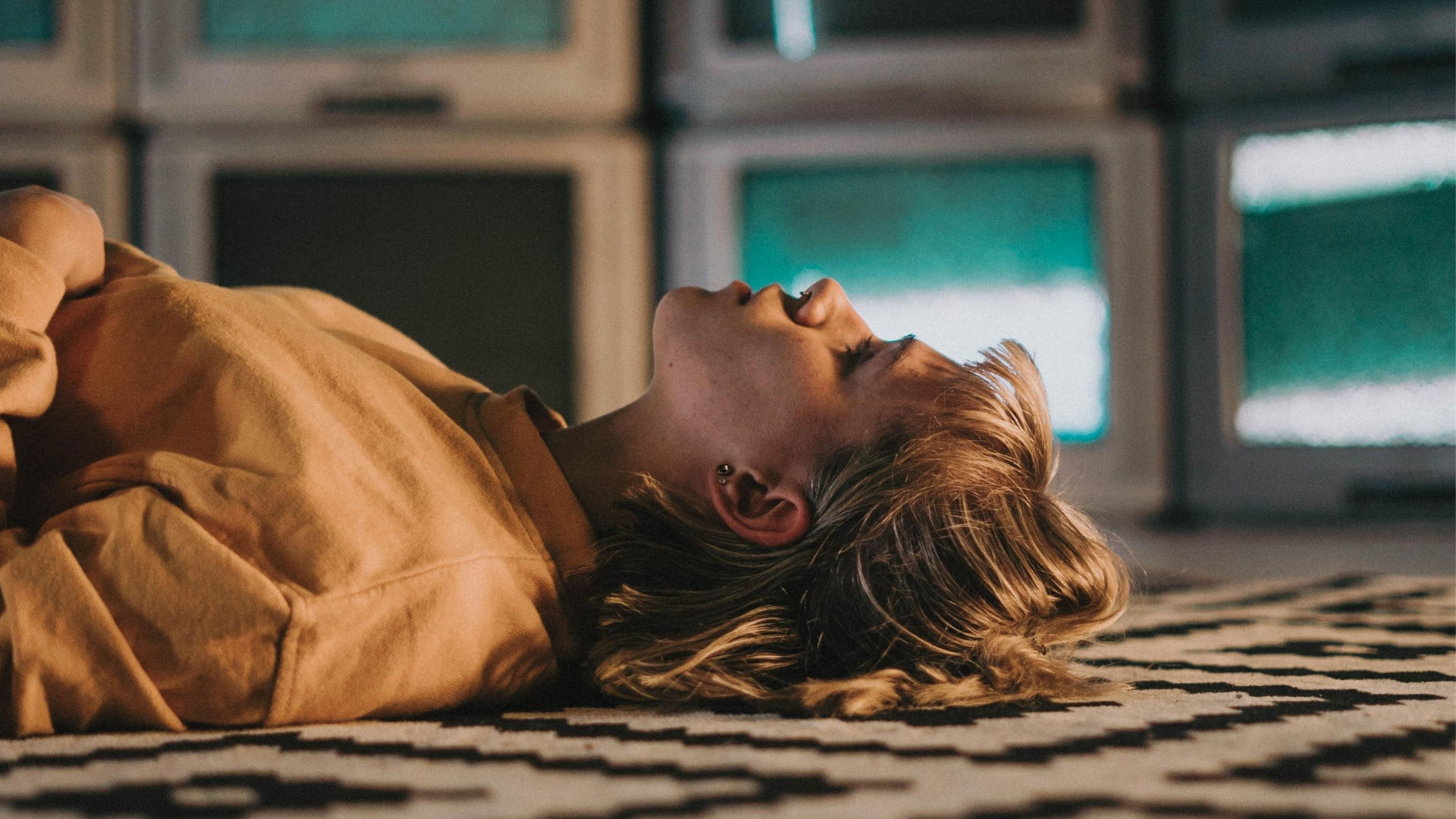 woman lying down in front of screens
